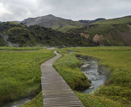 Wooden path to natural hot spring with group of tourist people relaxing in a thermal baths in Landmannalaugar camp site, Iceland. Grass meadow, lava fields and mountains in background.