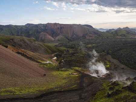 Colorful Rhyolit mountain panorma with multicolored volcanos and geothermal fumarole and in Landmannalaugar area of Fjallabak Nature Reserve in Highlands region of Iceland. Imagens