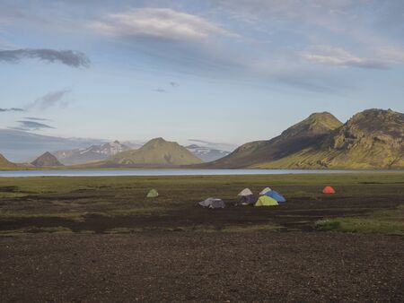 Colorful tents at camping site on blue Alftavatn lake with green hills and glacier in the otherwordly beautiful landscape of the Fjallabak Nature Reserve in the Highlands of Iceland. Part of famous Laugavegur hiking trail.
