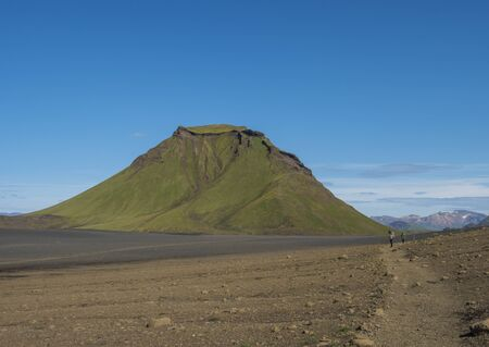 Panoramic view on green Hattafell mountain in Volcanic landscape behind Emstrur camping site with hikers on Laugavegur trek. Area of Fjallabak Nature Reserve in Highlands region of Iceland.