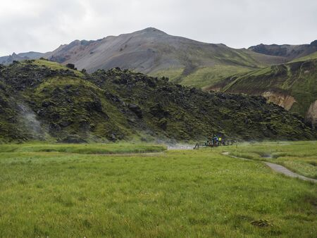 Group of tourist people relaxing in a natural hot spring in thermal baths in Landmannalaugar camp site, Iceland. Grass meadow, lava fields and mountains in background.