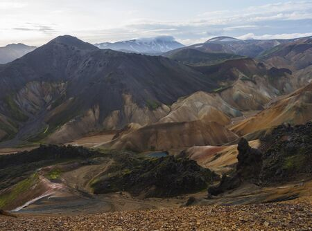 Colorful Rhyolit rainbow mountain panorma with multicolored volcanos and geothermal lake and snow covered peaks. Sunrise in Landmannalaugar at Fjallabak Nature Reserve, Highlands Iceland