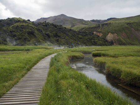 Wooden path to natural hot spring with group of tourist people relaxing in a thermal baths in Landmannalaugar camp site, Iceland. Grass meadow, lava fields and mountains in background