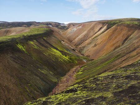 Colorful Rhyolit mountain panorma with multicolored volcanos and small creek in Landmannalaugar area of Fjallabak Nature Reserve in Highlands region of Iceland
