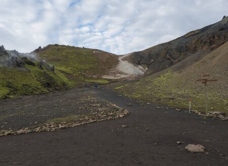 Hiker with blue backpack and tourist signpost at Laugavegur trek in Colorful Rhyolit rainbow mountain with multicolored volcanos and geothermal fumarole. Landmannalaugar at Fjallabak Nature Reserve, Highlands Iceland