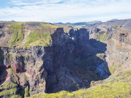 View on majestic Markarfljotsgljufur Canyon gorge and river with green moss covered hills near Botnar camp at Fjallabak Nature Reserve in Highlands of Iceland, blue sky background