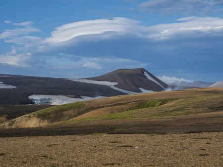 Colorful Rhyolit mountain panorma with snow fiields and multicolored volcanos in Landmannalaugar area of Fjallabak Nature Reserve in Highlands region of Iceland Imagens