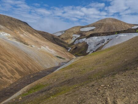 Orange Rhyolit mountains with snow fiields and spring from melted snow. Multicolored volcanos in Landmannalaugar area of Fjallabak Nature Reserve in Highlands region of Iceland
