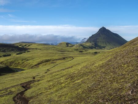 Volcanic landscape with footpath of Laugavegur trek and green Storasula mountain with lush moss and low clouds. Fjallabak Nature Reserve, Iceland. Blue sky background, copy space.