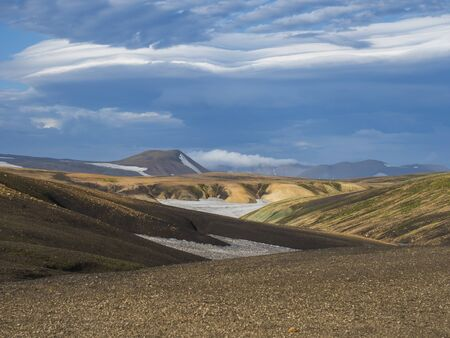 Colorful Rhyolit mountain panorma with snow fiields and multicolored volcanos in Landmannalaugar area of Fjallabak Nature Reserve in Highlands region of Iceland