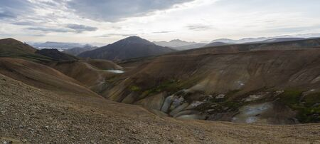 Colorful Rhyolit mountain panorma with multicolored volcanos and geothermal fumarole, lake and river delta. Sunrise in Landmannalaugar at Fjallabak Nature Reserve, Highlands Iceland