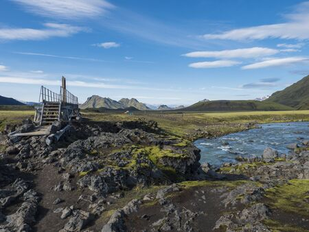 Landscape with wooden footbridge over a blue glacier river at laugavegur hiking trail in iceland. Lava formation and green hills and mountains, summer blue sky background