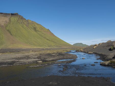 Blue river stream and green Hattafell mountain in Volcanic landscape behind Emstrur camping site in area of Fjallabak Nature Reserve in Highlands region of Iceland