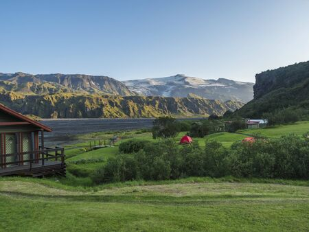 Mountain hut Skagfjordsskali and Langidalur camping site in Thorsmork with view on Godaland and Eyjafjallajokull glacier volcano and river Krossa. Highlands of Iceland, end of the Laugavegur hiking trail. Summer Golden hour.