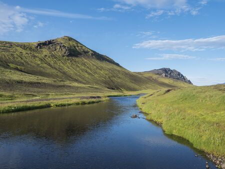 Beautiful green hills, lush grass and blue river next to camping site on Alftavatn lake. Summer sunny day, landscape of the Fjallabak Nature Reserve in Highlands Iceland part of Laugavegur hiking trail.