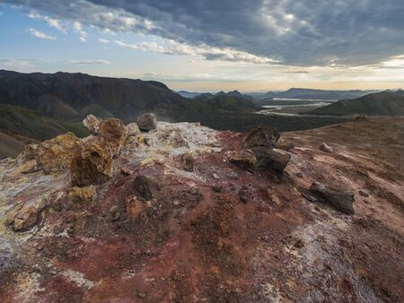 Colorful rhyolit red and orange fumarole at foot of Brennisteinsalda mountain with panorma of Landmannalaugar. Area of Fjallabak Nature Reserve in Highlands of Iceland Imagens