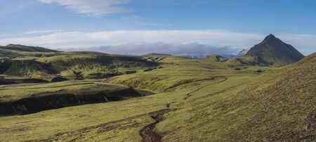 Panoramic volcanic landscape of green Storasula mountain with lush moss, footpath and blue creek water between Emstrur and Alftavatn camping sites on Laugavegur trek in area of Fjallabak Nature Reserve, Iceland Фото со стока