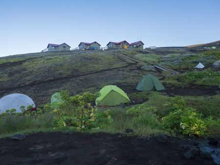 Colorful tents and Botnar mountain hut at Iceland on Laugavegur hiking trail, green valley in volcanic landscape among lava fields with view on Myrdalsjokull glacier. Early morning sunrise view.