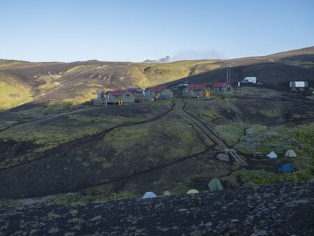 Colorful tents and Botnar mountain hut at Iceland on Laugavegur hiking trail, green valley in volcanic landscape among lava fields. Early morning sunrise view.