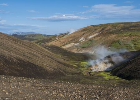 Landmannalaugar colorful Rhyolit mountains with steam from hot spring on famous Laugavegur trek. Fjallabak Nature Reserve in Highlands of Iceland, summer blue sky.