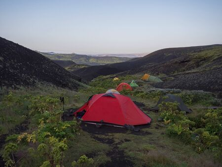 Colorful tents in Botnar campsite at Iceland on Laugavegur hiking trail, green valley in volcanic landscape among lava fields with view on Myrdalsjokull glacier. Early morning sunrise view.