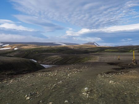 view on hiking path Laugavegur trail at Rhyolit Landmannalaugar mountain with snow fiields and multicolored volcanos at Fjallabak Nature Reserve in Highlands of Iceland Imagens