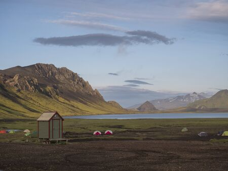 Colorful tents at camping site on blue Alftavatn lake with green hills and glacier in the otherwordly beautiful landscape of the Fjallabak Nature Reserve in the Highlands of Iceland part of famous Laugavegur hiking trail.