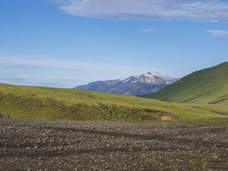 Volcanic landscape with snow-capped mountains of Tindfjallajokull glacier massif, green hills and lava gravel ground covered by lush moss. Fjallabak Nature Reserve in the Highlands of Iceland