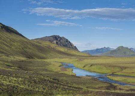 Beautiful green hills, lush grass and blue river with footbridge next to camping site on Alftavatn lake. Summer sunny day, landscape of the Fjallabak Nature Reserve in Highlands of Iceland part of Laugavegur hiking trail.