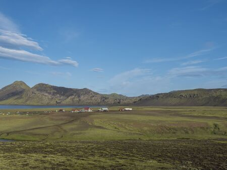 Landscape with mountain huts at camping site on blue Alftavatn lake with river, green hills and glacier in beautiful landscape of the Fjallabak Nature Reserve in the Highlands of Iceland part of Laugavegur hiking trail.