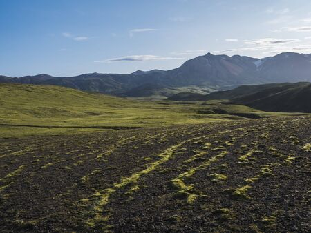 Volcanic landscape with snow covered mountains, green hills and lava gravel ground covered by lush moss. Fjallabak Nature Reserve in the Highlands of Iceland Imagens