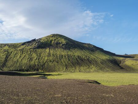 Beautiful green volcanic hill with lush moss and grass near Alftavatn lake. Summer sunny day, landscape of the Fjallabak Nature Reserve in Highlands Iceland