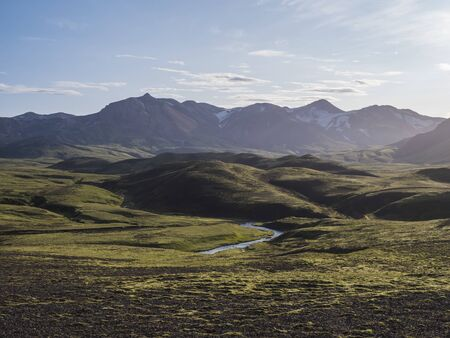 Volcanic landscape with blue river, snow covered mountains, green hills and lava gravel ground covered by lush moss. Fjallabak Nature Reserve in the Highlands of Iceland