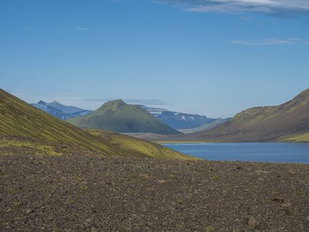 Beautiful landscape of blue Alftavatn lake with snow covered mountains and green hills and blue sky background. Summer landscape of the Fjallabak Nature Reserve in the Highlands of Iceland. Copy space.