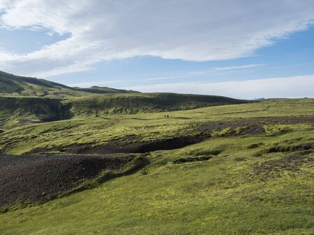Two hikers backpack travelers in volcanic landscape with green hills, meadow and lava gravel ground covered by lush moss. Fjallabak Nature Reserve in the Highlands of Iceland. Summer blue sky