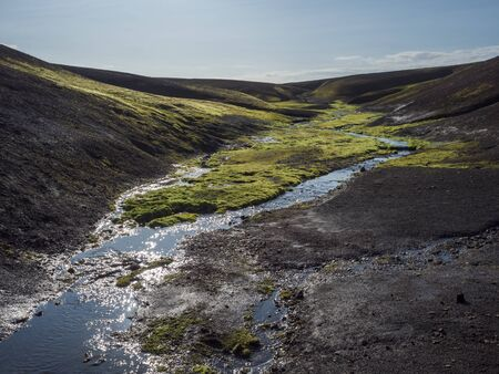 Small stream from melting ice with Lush vivid green wet moss in black lava hills in Landmannalaugar mountain. Fjallabak Nature Reserve in Highlands of Iceland, summer blue sky.