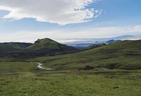 Icelandic landscape with Tindfjallajokull glacier, green hills, river stream and lush grass and moss. Laugavegur hiking trail, Fjallabak Nature Reserve, Iceland. Summer blue sky