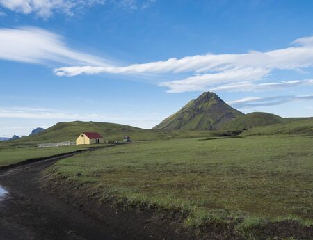 Ancient farm houses near the Hvanngil camp site with green storasula montain onLaugavegur hiking trail, Highlands of Iceland