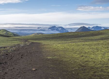 Icelandic landscape with footpath of Laugavegur hiking trail with view on Tindfjallajokull glacier, green hills and lava gravel ground covered by grass and moss. Fjallabak Nature Reserve, Iceland