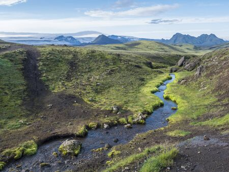 Volcanic landscape with mountains of Tindfjallajokull glacier massif, green hills and blue creek water with lush moss. Fjallabak Nature Reserve, celand. Summer blue sky