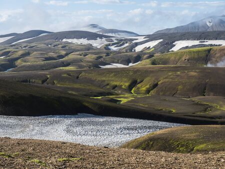 Landmannalaugar colorful Rhyolit mountains with snow fiields on famous Laugavegur trek. Fjallabak Nature Reserve in Highlands of Iceland, summer blue sky. Imagens