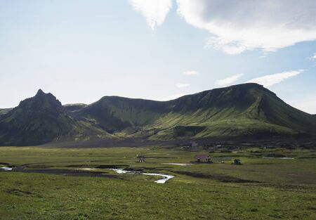 view on Hvanngil mountain hut and camp site with green hills, river stream and lush grass and moss. Laugavegur hiking trail, Fjallabak Nature Reserve, Iceland. Summer blue sky Фото со стока