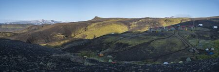 Panoramic landscape with botnar mountain hut at Iceland on Laugavegur hiking trail, green valley in volcanic landscape among lava fields. Early morning, summer blue sky Stok Fotoğraf