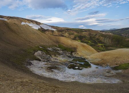 Panorma of Colorful Rhyolit Landmannalaugar mountain with multicolored volcanos and sulphur pool with geothermal fumarole at Fjallabak Nature Reserve in Highlands of Iceland