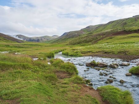 Reykjadalur valley with hot springs river with lush green grass meadow and hills with geothermal steam. South Iceland near Hveragerdi city. Summer sunny morning, blue sky.