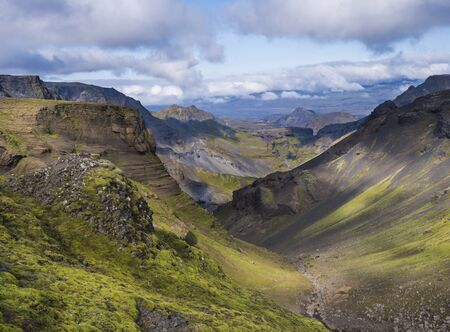 Landscape of Godland and thorsmork with rugged green moss covered rocks and hills, bending river canyon, Iceland, Fimmvorduhals hiking trail. Summer blue sky white clouds