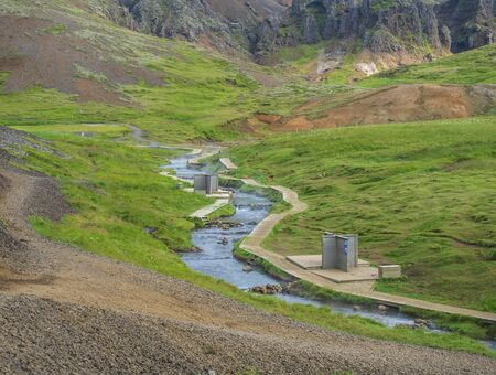 Natural geothermal bath in a Hot River stream in Reykjadalur Valley with wooden footpath and changing rooms. South Iceland near Hveragerdi city. Summer sunny morning.