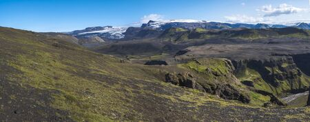 Panoramic landscape with blue Markarfljot river canyon, green hills and eyjafjallajokull volcano glacier. Laugavegur hiking trail. Fjallabak Nature Reserve, Iceland. Summer blue sky.