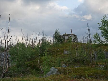 Abadoned Sami hut Goathi in green hills landscape of Abisko National Park. Goahti is Lappish traditional dwelling made from fabric, peat moss and timber. Lapland, Northern Sweden on Kungsleden trail. Summer sunny day. Banco de Imagens