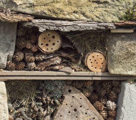 Hausgemachtes Insektenhotel dekoratives Insektenhaus aus Sandstein und Holz, Marienkäfer und Bienenhaus für Schmetterlingsüberwinterung und ökologische Gartenarbeit. Konzept zum Schutz von Insekten Standard-Bild